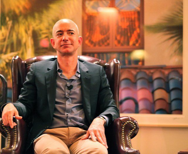Jeff Bezos sitting in chair with colorful background